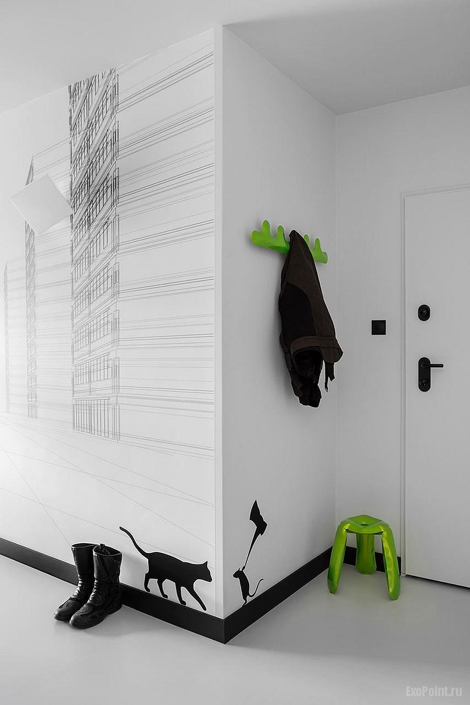 décalcomanies murales en noir et blanc et touches de vert vives vous souhaitent la bienvenue à l'entrée de l'appartement