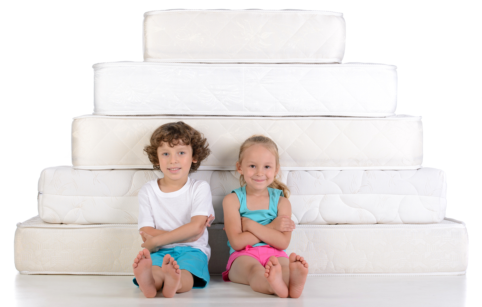 Unge børn sidder på masser af madrasser isoleret på hvid baggrund